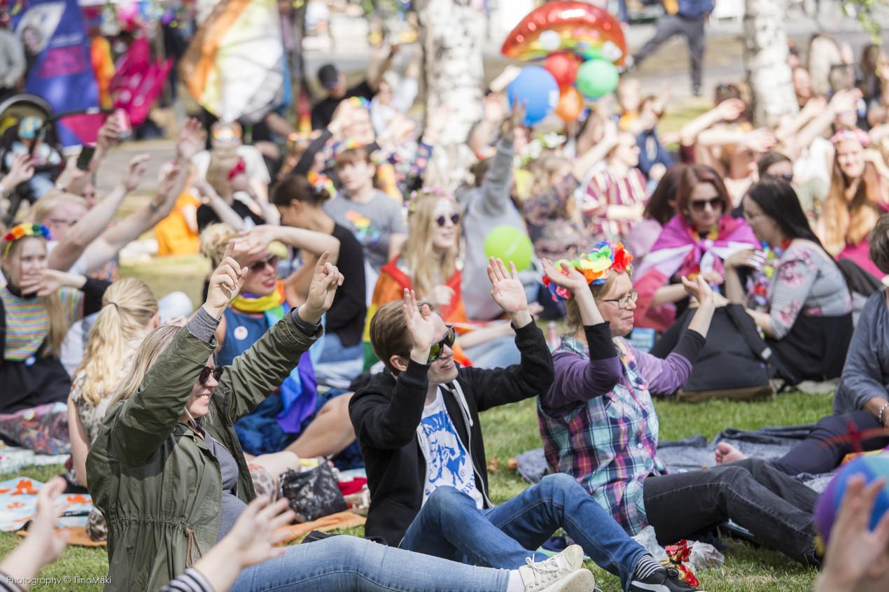 Ihmisiä istumassa nurmella Oulu Priden puistojuhlassa.